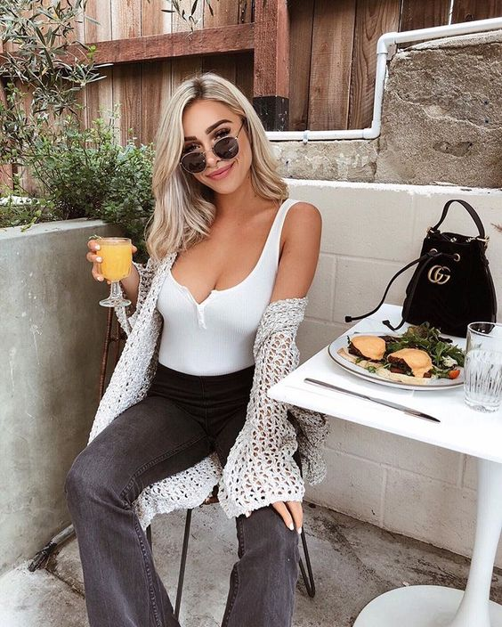a white top, black flare jeans, a grey crochet cardigan and a small black bag