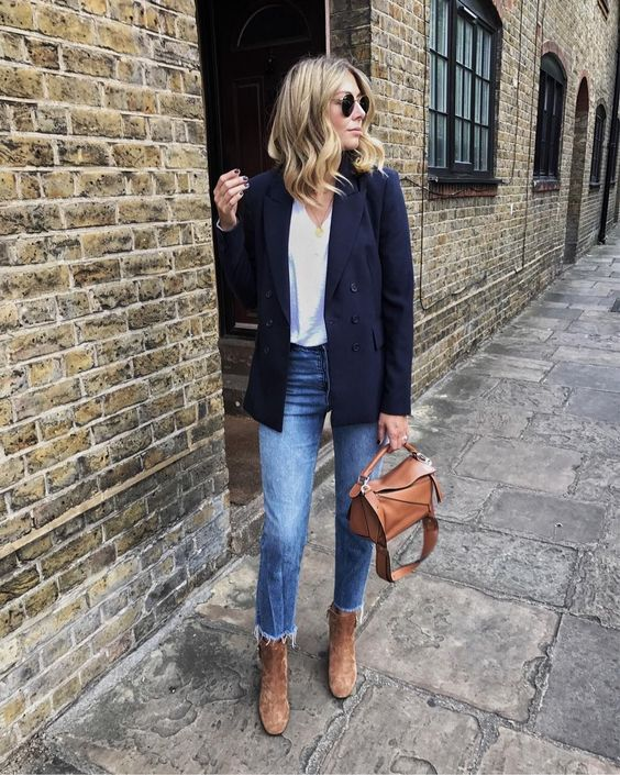 a white top, blue jeans with a ripped hem, a navy blazer, brown velvet boots and a brown bag