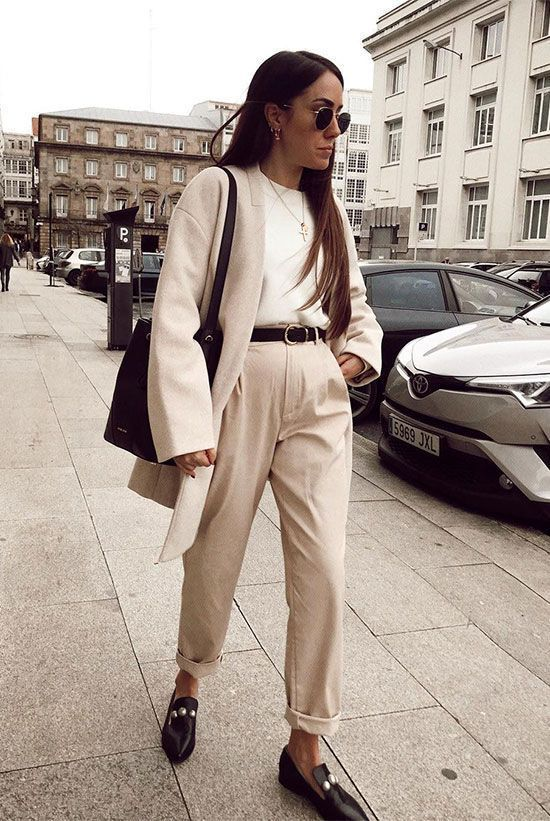 a white top, tan trousers, a light-colored short coat, black embellished mules and a black tote