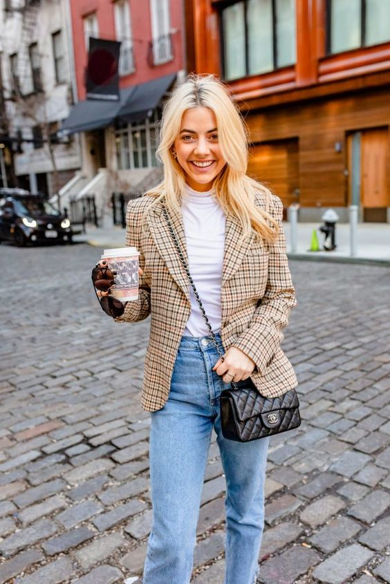 a white turtleneck, blue straight leg jeans, a tan plaid blazer and a black crossbody bag is classics for work