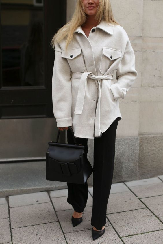 a work outfit with a black top, pants, an off-white shirt jacket, black heels and a black bag for work
