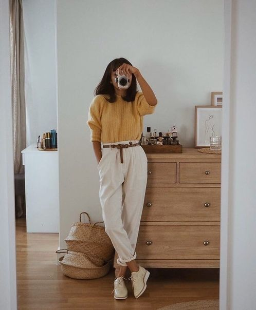 a yellow jumper, white high waisted pants, white platform shoes and a brown belt