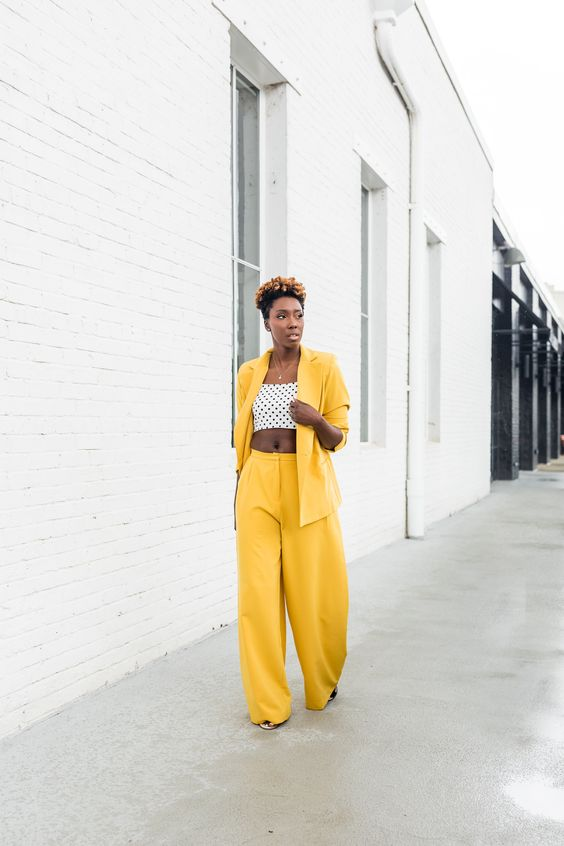 a yellow pantsuit with wideleg pants, a polka dot crop top and an oversized blazer