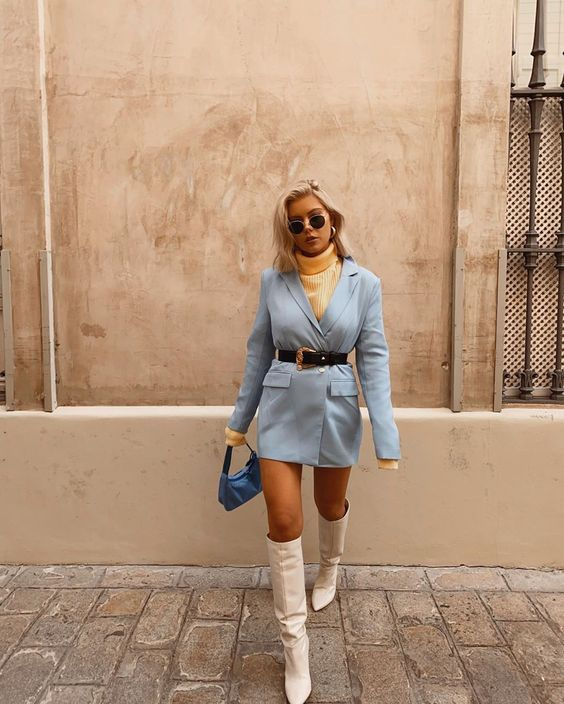 a yellow turtleneck, a blue blazer worn as a dress, a black belt, white boots and a blue baguette bag