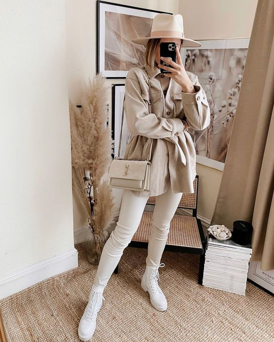 an all-neutral look with a neutral shirt, skinnies, white boots, a neutral shirt jacket, a hat and a bag