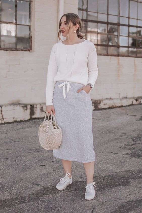an early spring outfit with a white jumper, a grey sporty midi skirt, grey sneakers and a round wicker bag