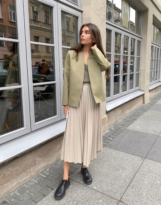 an office look with a taupe top, a green jacket, a grey pleated midi skirt, black Derby shoes