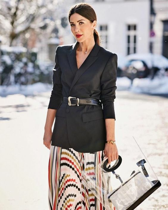 an oversized black blazer with a black belt, a colorful print midi skirt, a creative bag with a sheer part