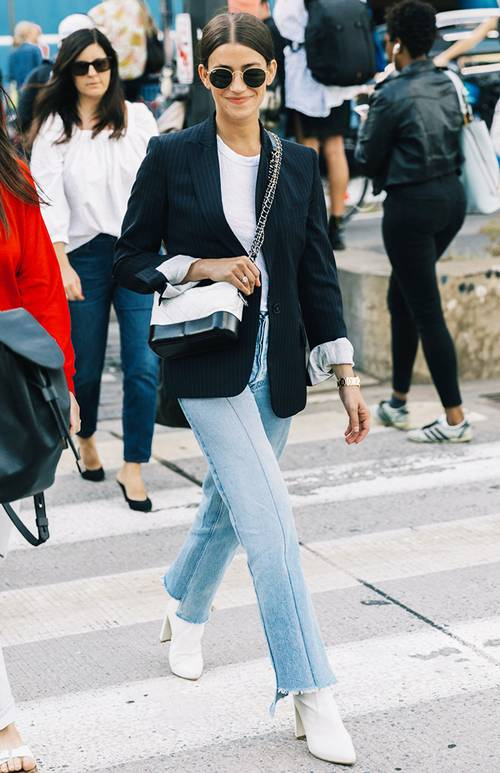blue jeans, a white t-shirt, a black tailored blazer, white boots and a two tone bag