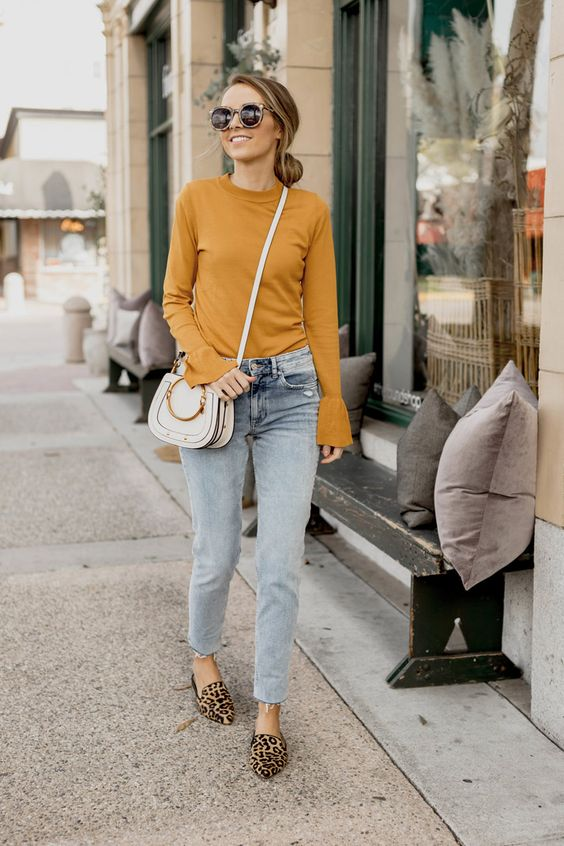 light blue mom jeans, a mustard top with bell sleeves, leopard print flats and a white bag