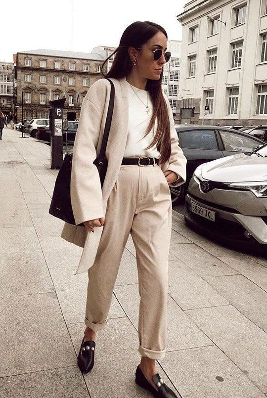 neutral pants, a white tee, black loafers, a black belt, a neutral short coat and a black tote