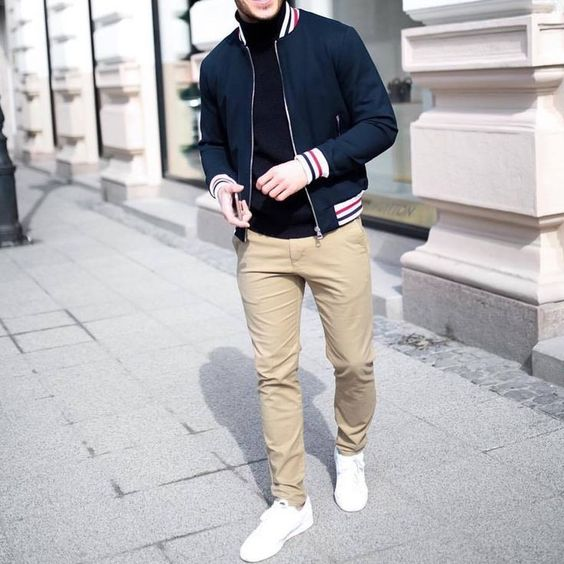 tan jeans, white sneakers, a black turtleneck and a navy bomber jacket for a spring date look