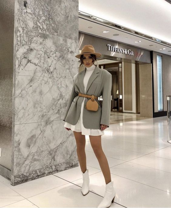white cowboy boots, a white dress with a turtleneck, a grey oversized blazer, a tan hat and a waist bag
