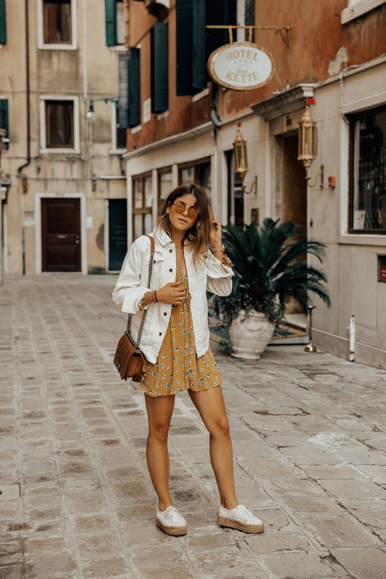a mustard floral mini dress, platform sneakers, a white denim jacket, a brown bag and sunglasses