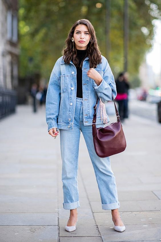 a simple look with a black turtleneck, blue straight jeans, an oversized denim jacket, white shoes and a burgundy bag