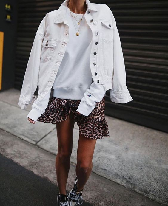 a white sweatshirt, a leopard mini skirt, a denim jacket, black trainers and layered necklaces