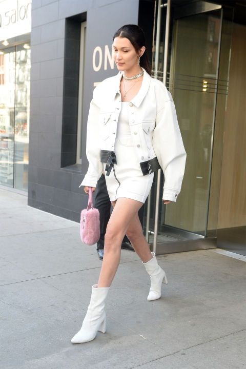 11 Bella Hadid wearing a white mini dress, an oversized white denim jacket, white boots and a pink bag