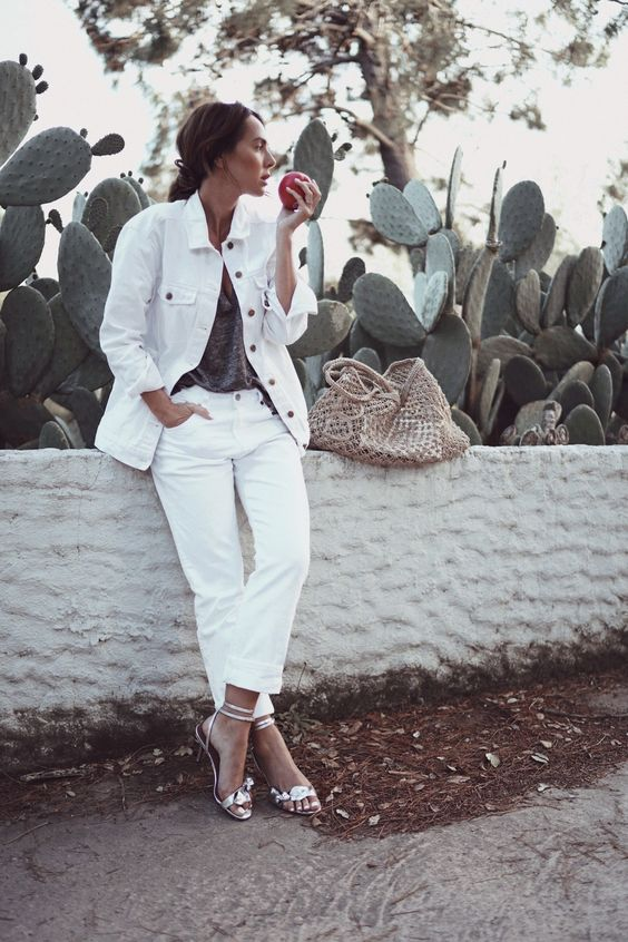 white jeans paired with an oversized white denim jacket, a grey tee, silver heels and a woven bag for summer