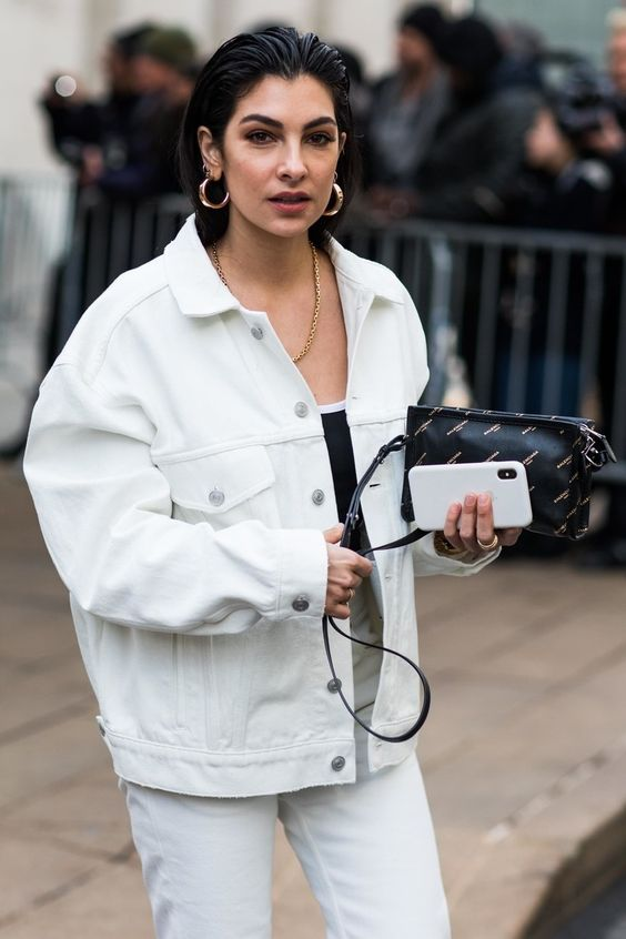 white jeans, a white oversized denim jacket, a black top, a black clutch and statement accessories