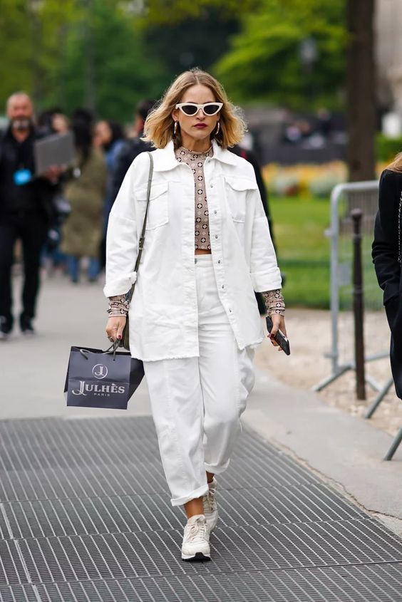 27 white jeans, an oversized denim jacket, a printed crop top, white trainers and a grey bag
