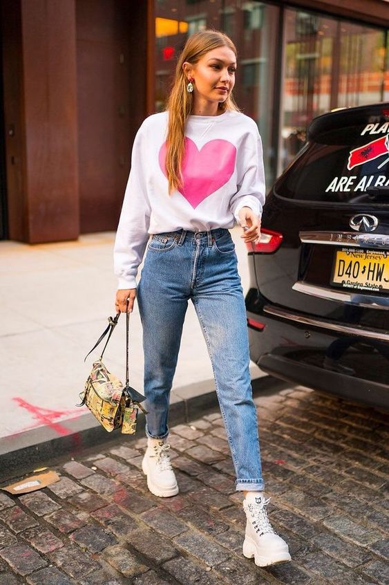 Gigi Hadid wearing a white sweatshirt, blue mom jeans, white boots and a colorful bag