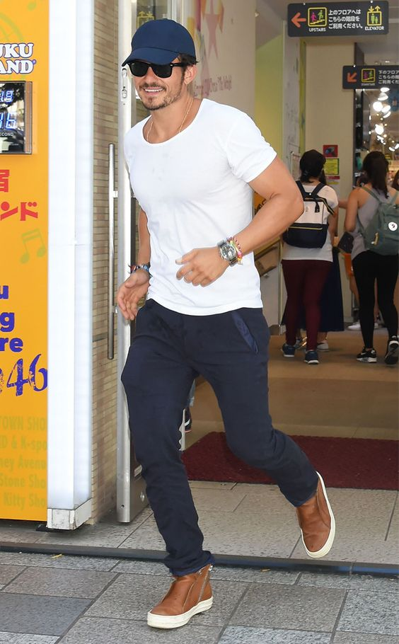 Orlando Bloom wearing a white tee, navy pants, brown boots and a navy baseball cap