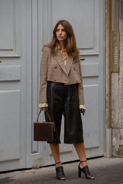 With beige shirt, black leather culottes, brown leather bag and black high heels