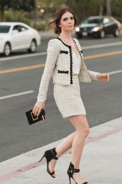 With beige top, black clutch and black high heels