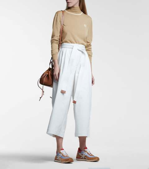 With beige turtleneck sweater, brown bag and colorful sneakers