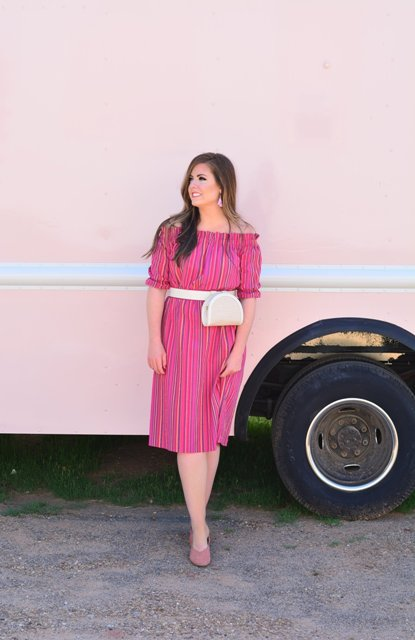 With beige waist bag and pale pink mules