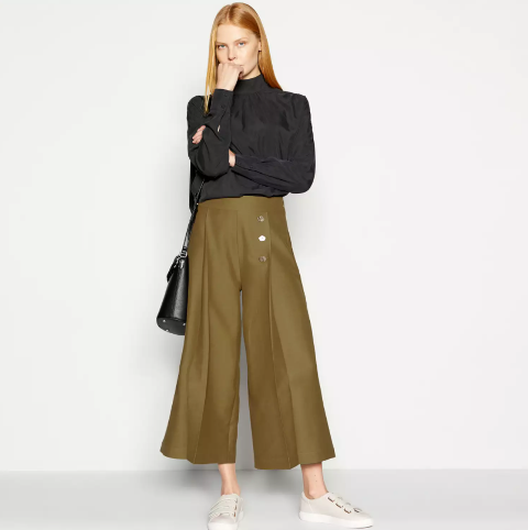 With black loose turtleneck, black leather bag and beige flat shoes