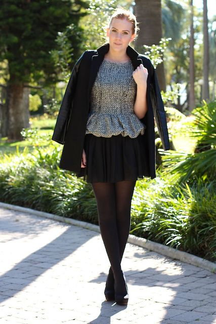 With black pleated mini skirt, black jacket and platform shoes