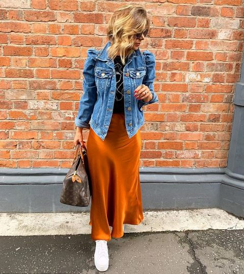 With black shirt, orange maxi skirt, printed bag and white sneakers