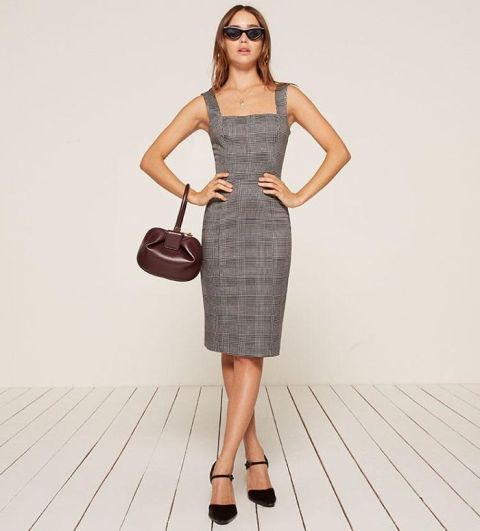 With black shoes, sunglasses and brown leather bag