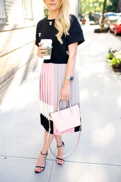 With black t shirt, pale pink bag and black ankle strap high heels