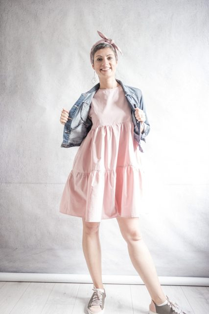 With denim crop jacket and pale pink and gray sneakers