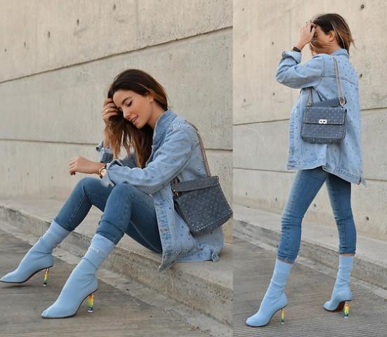 With denim embellished jacket, skinny jeans and blue bag