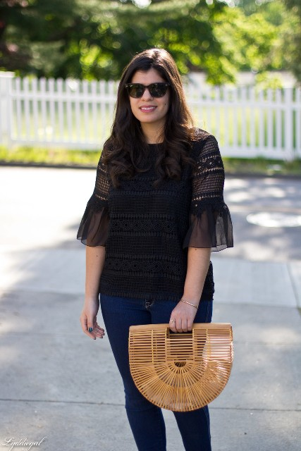 With navy blue skinny jeans and straw bag