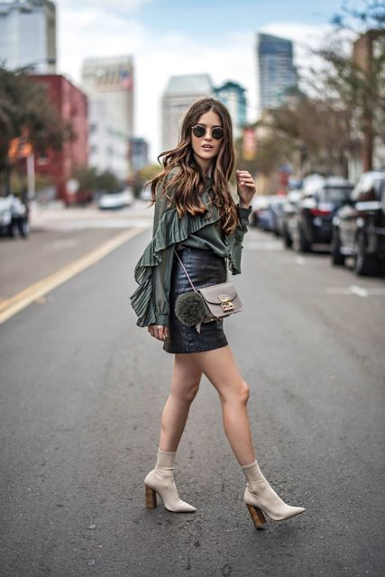 With olive green ruffled blouse, black leather skirt and gray bag