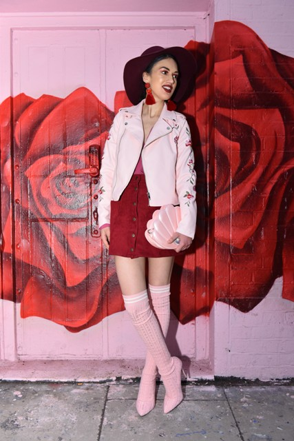 With pink top, pale pink floral jacket, red button front skirt, hat and clutch