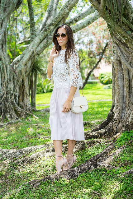 With pleated skirt, white bag and ankle strap shoes