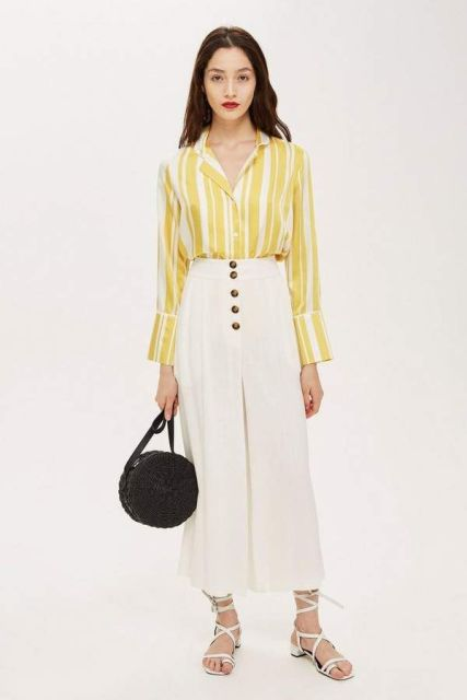 With white and yellow striped shirt, black rounded bag and white lace up sandals