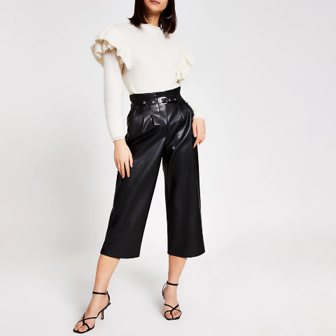 With white ruffled sweater and black ankle strap sandals