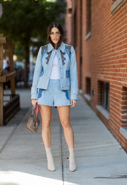 With white shirt, light blue shorts, blazer and printed bag