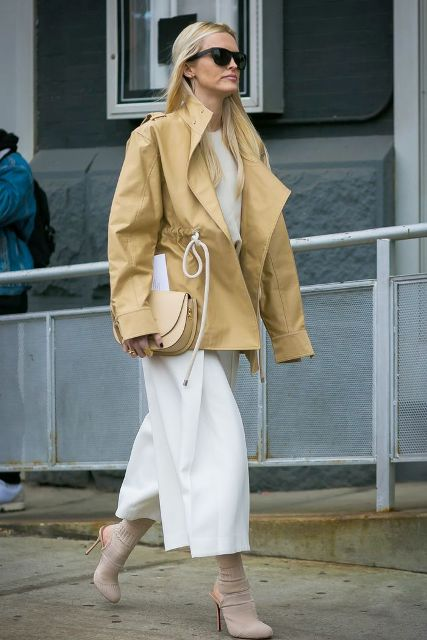 With white shirt, white culottes, beige belted jacket and beige leather clutch