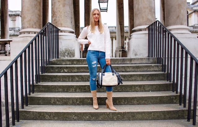 With white sweater, distressed jeans and tote bag