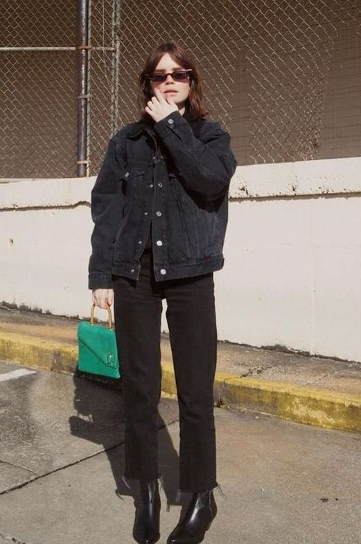 a black denim jacket, black jeans, black boots and a bold green bag to refresh the space