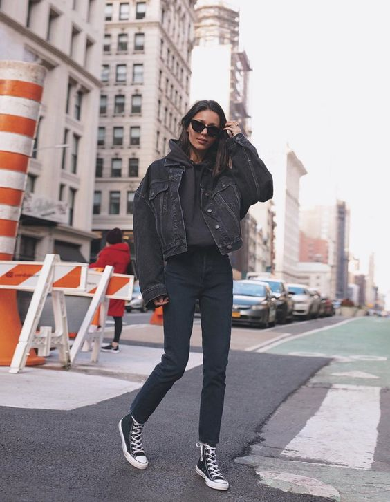 a black hoodie, a black denim jacket, navy jeans, black sneakers for a comfy everyday look