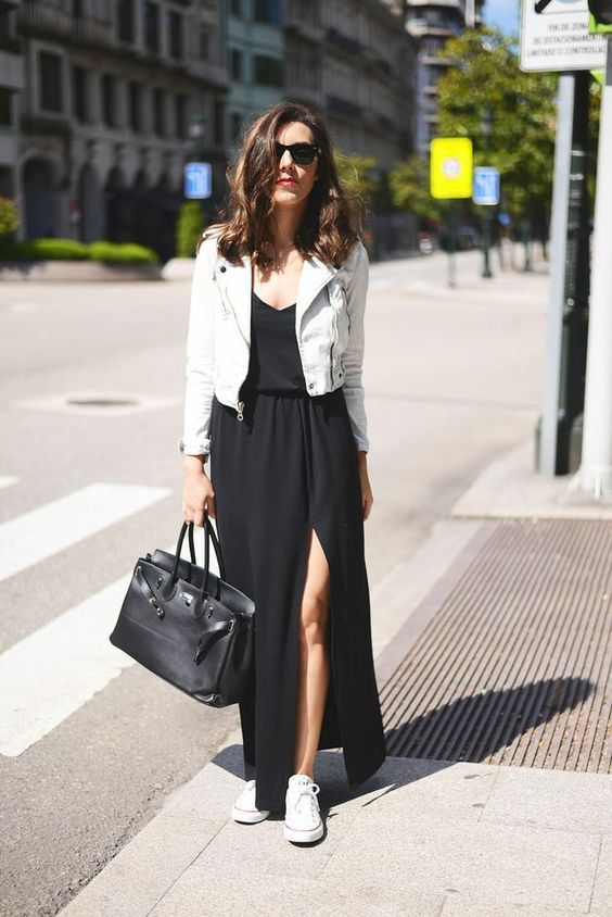 a black maxi dress with a front slit, white sneakers, a white cropped leather jacket and a black bag