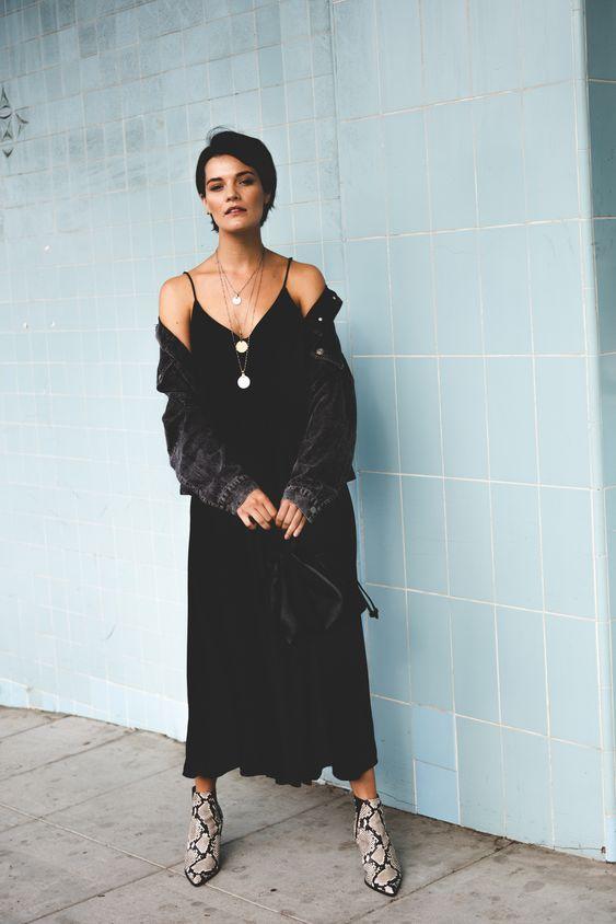 a black slip midi dress, a black denim jacket, snakeskin print boots and a black bag for a boho look